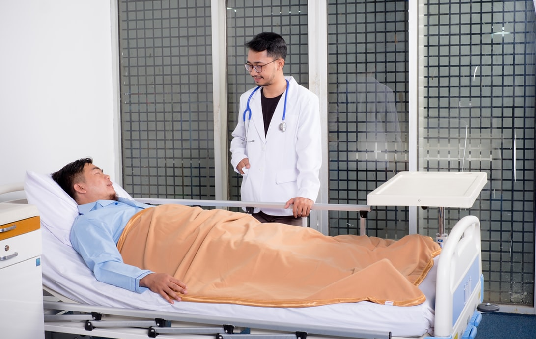 man in hospital bed talking to doctor