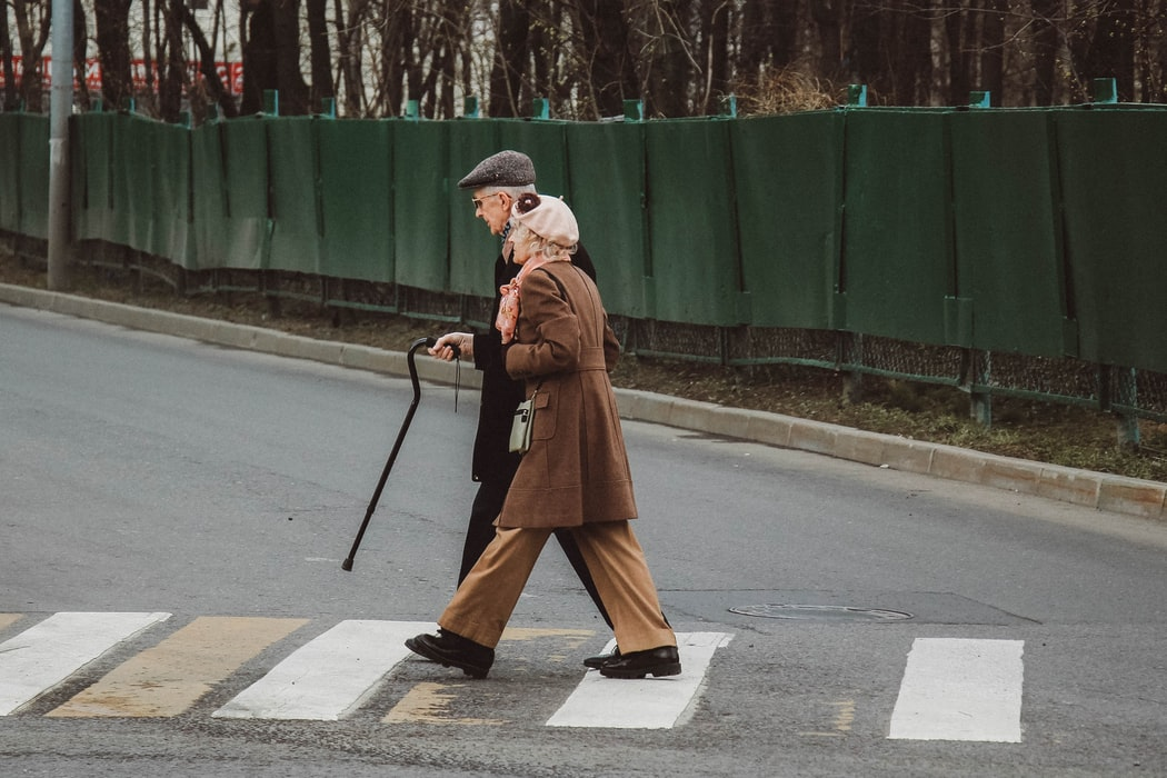 old man and old woman walking down the street